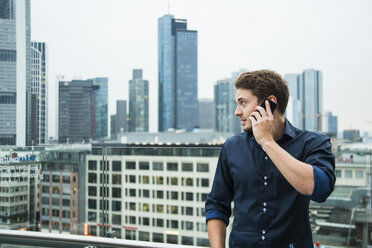 Germany, Hesse, Frankfurt, young man telephoning with his smartphone in front of the skyline - UUF001844