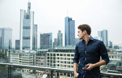 Germany, Hesse, Frankfurt, young man with his smartphone standing in front of the skyline - UUF001845
