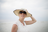 Smiling woman wearing straw hat and sunglasses outdoors - NNF000024