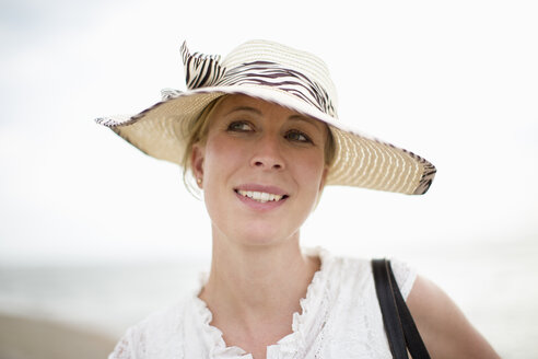 Smiling woman wearing straw hat outdoors - NNF000025