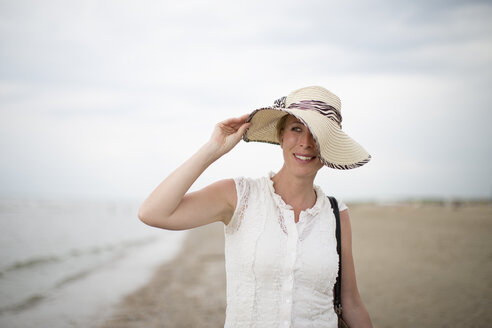 Netherlands, Noordwijk, smiling woman wearing straw hat on the beach - NNF000026