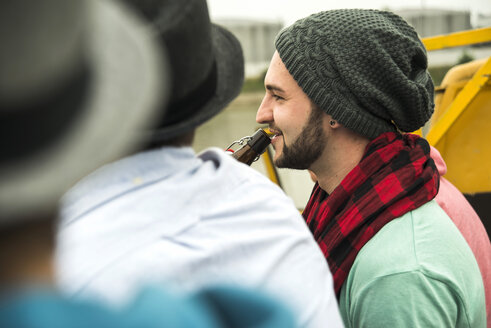 Group of friends drinking beer outdoors - UUF001853