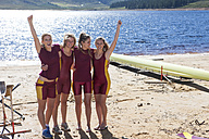 Four female rowers cheering at lakeshore - ZEF000932