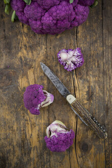 Purple cauliflower florets and a pocket knife on wood - LVF001893
