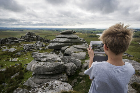UK, Cornwall, boy photographing landscape at Bodmin Moor with his digital tablet - PAF000972