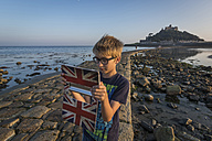 UK, Cornwall, boy taking a selfie in front of St. Michael's Mount with his digital tablet - PAF000964