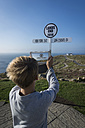 UK, Cornwall, boy photographing direction sign at Land's End with his digital tablet - PAF000969