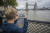 UK, London, boy taking picture with digital tablet at Tower Bridge - PAF000977