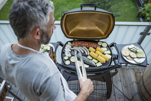 Man barbecuing on his balcony - MBEF001276