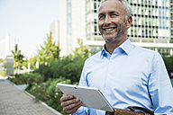 Smiling businessman holding digital tablet outdoors - UUF001934