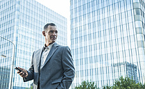 Mature businessmanwith cell phone outside office building - UUF001943