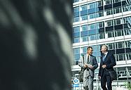Two businessmen talking outside office building - UUF001946