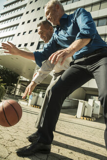 Two businessmen playing basketball outside office building - UUF001963