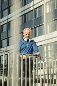 Businessman with digital tablet  and headphones outside office building - UUF001974