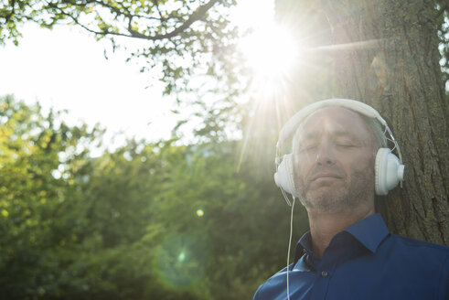 Mature man leaning against tree trunk listening to music - UUF001964