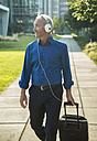 Businessman with suitcase and headphones walking on pavement - UUF001967