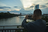 Germany, Frankfurt, man on bridge taking a picture - UUF001991