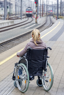 Woman in wheelchair waiting at station platform - EJWF000605