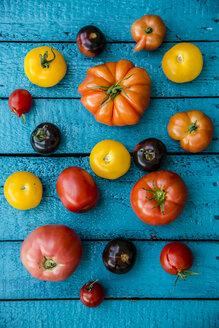 Different heirloom tomatoes on blue wood - SARF000849