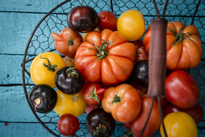 Different heirloom tomatoes in a wire basket - SARF000853