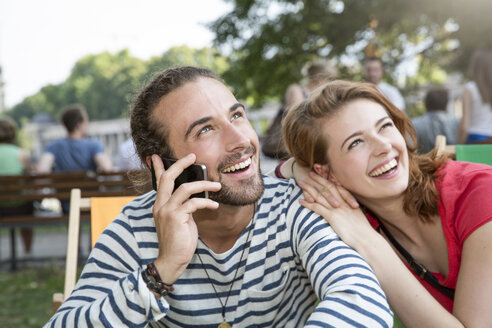 Germany, Berlin, Young couple walking in park, using smart phone - FKF000652