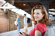 Germany, Berlin, Young woman using smart phone at train station - FKF000658