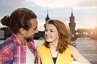 Germany, Berlin, Young couple enjoying sunset at Spree river - FKF000673