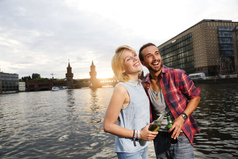 Germany, Berlin, Young couple enjoying sunset at Spree river - FKF000676