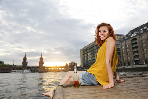Germany, Berlin, Young woman enjoying sunset at Spree river - FKF000678
