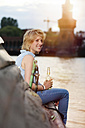 Germany, Berlin, Young woman enjoying sunset at Spree river - FKF000680