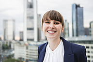 Germany, Hesse, Frankfurt, portrait of smiling businesswoman in front of skyline - FMKYF000518