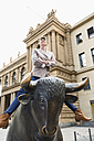 Germany, Hesse, Frankfurt,  businesswoman with crossed arms sitting on bull sculpture in front of stock market - FMKYF000528