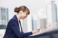 Germany, Hesse, Frankfurt, smiling businesswoman using her smartphone - FMKYF000535