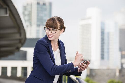 Germany, Hesse, Frankfurt, portrait of smiling businesswoman with glasses holding smartphone - FMKYF000537