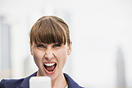 Portrait of screaming businesswoman with smartphone - FMKYF000540