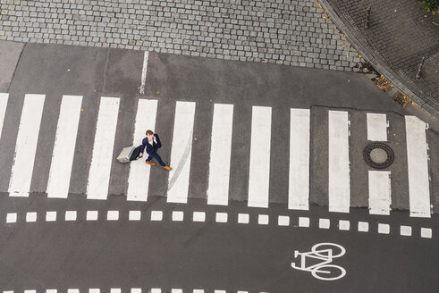 Germany, businesswoman with rolling suitcase walking on zebra crossing, view from above - FMKYF000550