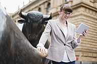 Germany, Hesse, Frankfurt, businesswoman with digital tablet standing in front of stock market - FMKYF000567