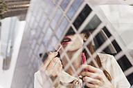 Businesswoman applying lipstick, partial view - FMKYF000595