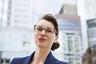 Germany, Hesse, Frankfurt, portrait of smiling businesswoman with glasses standing in front of office buildings - FMKYF000605