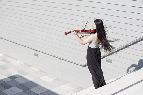 Young female Asian playing violin on stairs - MAD000013