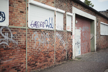 Germany, Saxony, Leipzig, graffiti on facade and closed roller shutters of an old industry building - DWF000178