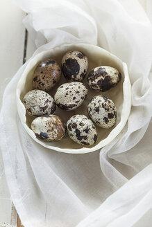Bowl of quail eggs on white cloth and  wood - SBDF001251