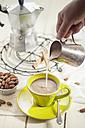Woman's hand pouring almond milk into cup of coffee - SBDF001259