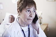 Serious doctor on the phone with patient in hospital bed - ZEF000963