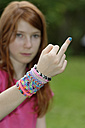 Girl with looms at her wrist giving the finger - LBF000956