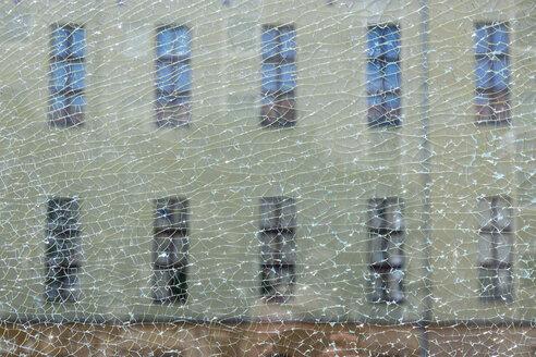 Germany, Berlin, view through broken glass pane to facade - WIF001087