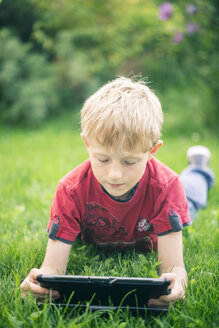 Boy lying on a meadow using digital tablet - SARF000864