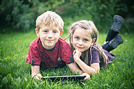 Portrait of brother and sister lying on a meadow with digital tablet - SARF000868