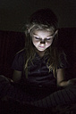 Portrait of little girl sitting in darkness using digital tablet - SARF000869