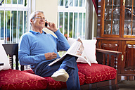 Senior man on the phone reading newspaper at home - ZEF001048